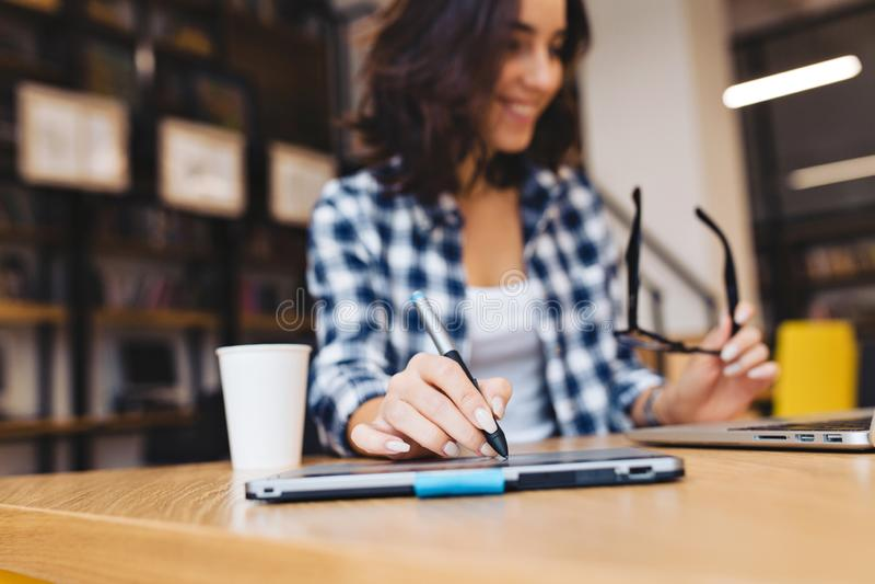 Pracuje kreatywnie czas młody brunetki dziewczyny studiowanie z laptopem w bibliotece Nowożytny uczeń, ostrość na ręce, bawić się obrazy royalty free