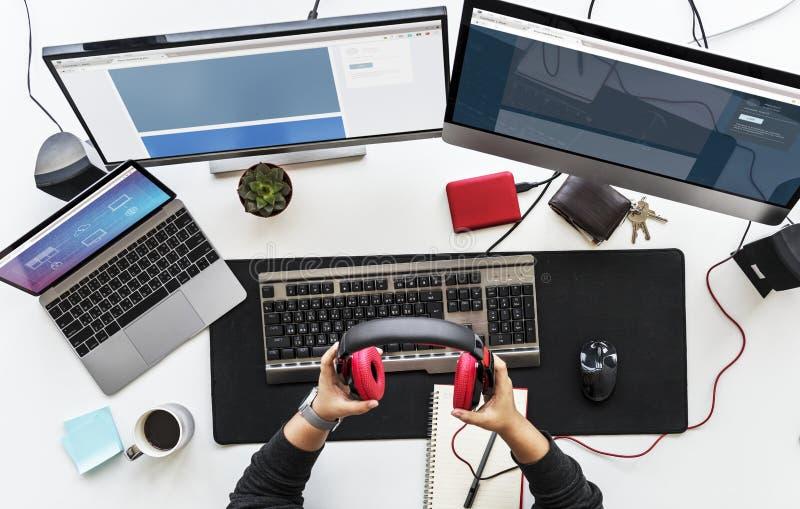 Pracy biurko z wielokrotność urządzeniami elektronicznymi i ekranami zdjęcia stock