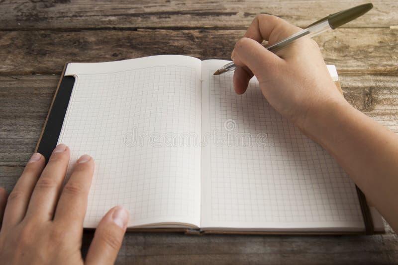 Pracy i czasu zarządzanie planistyczny dzienniczek i ludzka ręka, trzyma pióra zakończenie nad rozpieczętowaną nutową książką Wie obrazy stock
