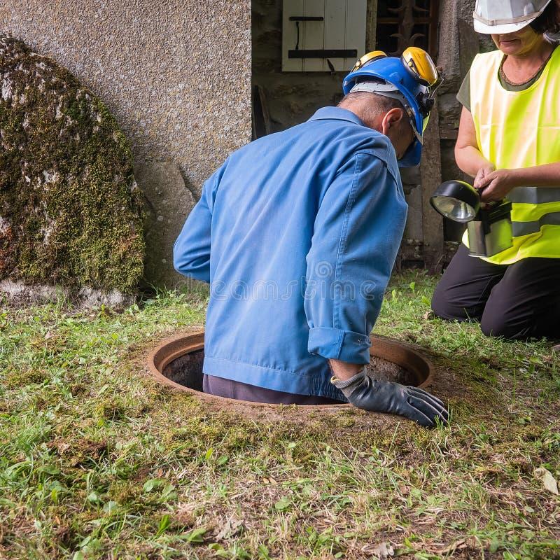 Pracy w manhole drużyną mężczyzna i kobieta zdjęcie royalty free
