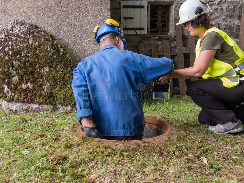 Pracy w manhole drużyną mężczyzna i kobieta zdjęcia royalty free