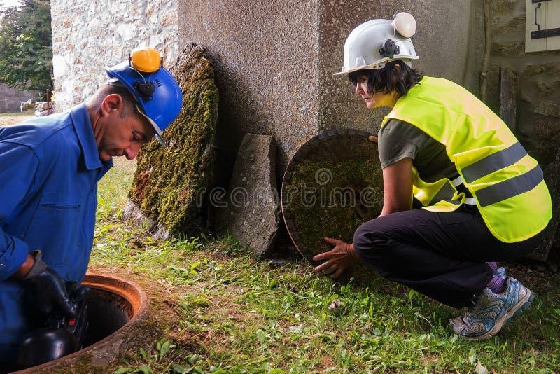 Pracy w manhole drużyną mężczyzna i kobieta obraz royalty free