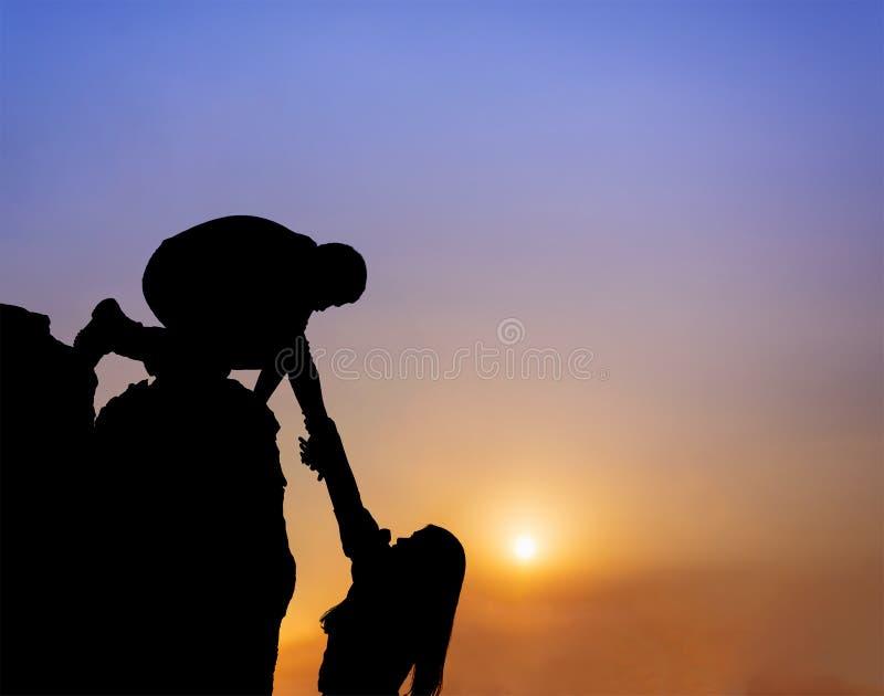 Pracy zespołowej pary pomocnej dłoni zaufania pomocy sylwetka w górach, zmierzch fotografia royalty free