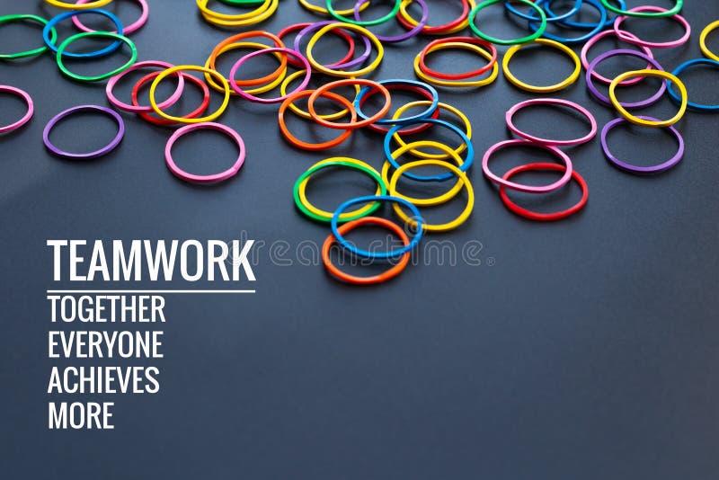 Pracy zespołowej pojęcie grupa kolorowy gumowy zespół na czarnym tle z słowo pracą zespołową, Wpólnie, Everyone, Dokonuje i Więce fotografia stock
