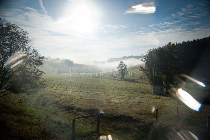 Prado con una pequeña capilla cubierta por el sol y la neblina fotos de archivo