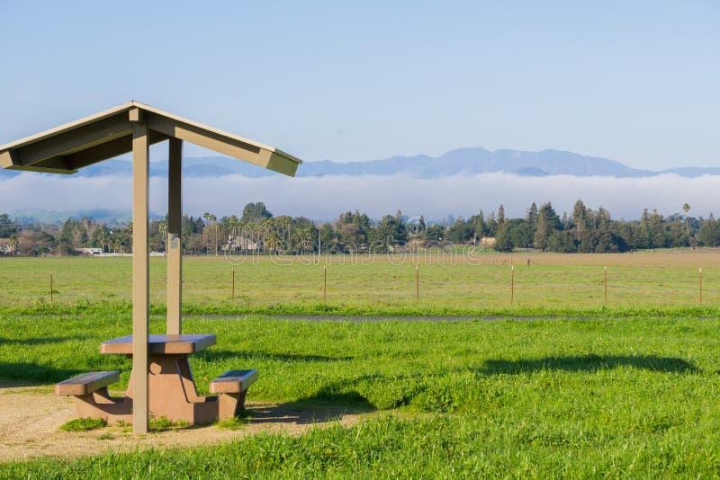 Prado da tabela de piquenique e da grama verde; névoa atrasando-se no fundo, lago coyote - Harvey Bear Park, Morgan Hill, Califór fotografia de stock