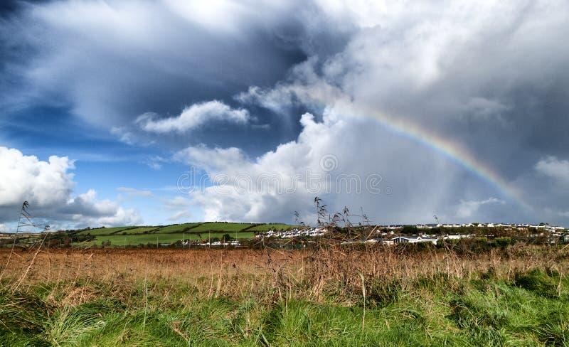Prado irlandês com grama alta e um arco-íris imagem de stock