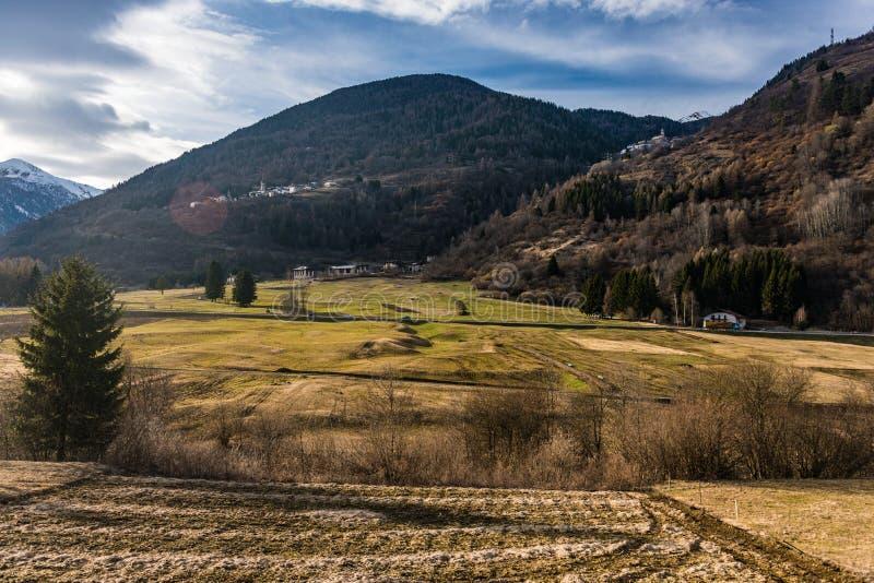 Prado soleado en las montañas italianas, Dolomities, Val di Sole de la primavera imagenes de archivo