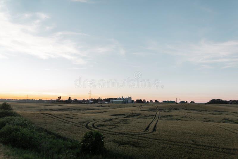 Prado verde con una granja en el fondo el cielo azul y la puesta del sol rosada del verano F?brica Agricultura fotografía de archivo libre de regalías