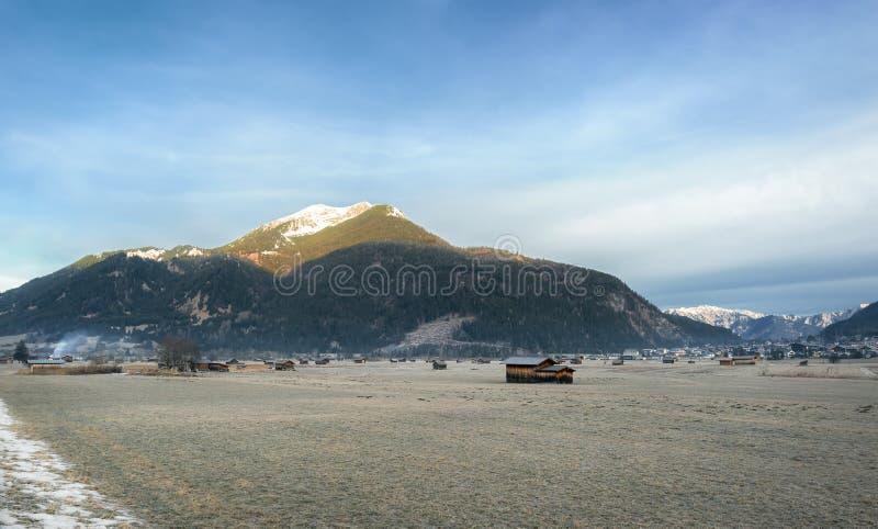 Prado y pueblo congelados en las montañas fotografía de archivo libre de regalías