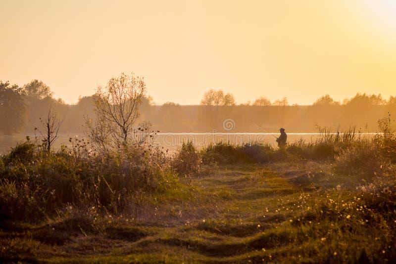 Prado y río durante la puesta del sol Pescador con un tac pesquero foto de archivo libre de regalías