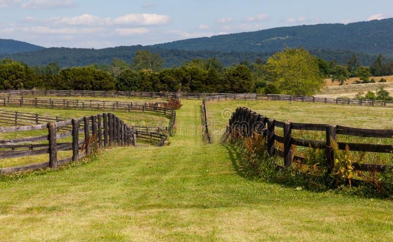 Prados del balanceo con las cercas y las colinas de madera foto de archivo