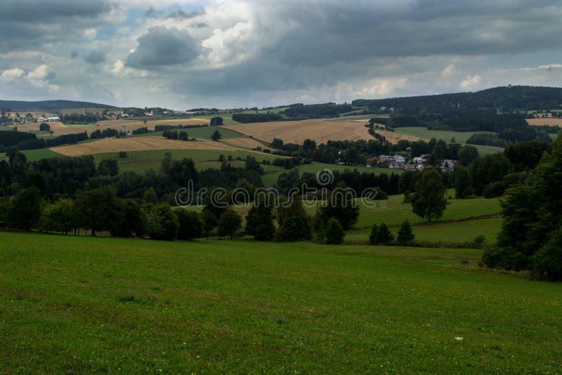 Prados verdes, campos amarillos y bosques debajo de las nubes de tormenta foto de archivo
