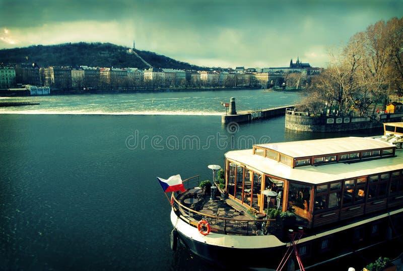Prag mit Boot auf Vltava Fluss lizenzfreie stockfotografie