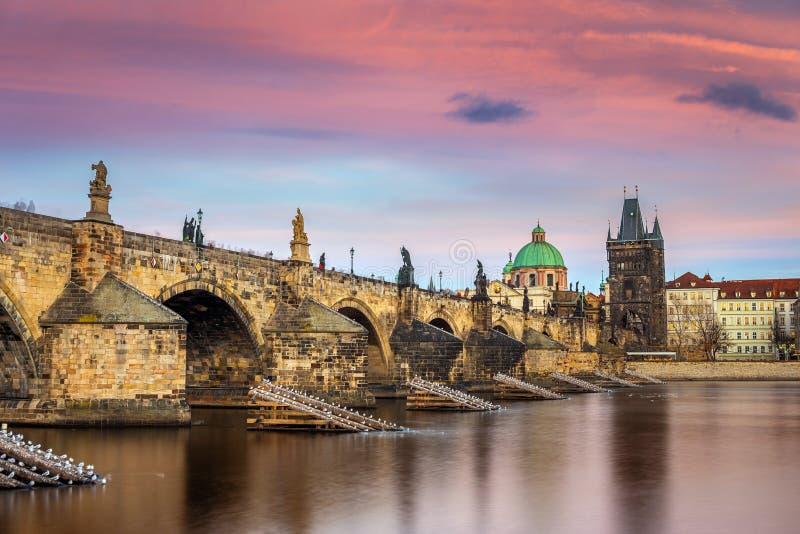 Prag, Tjeckien - Världen berömde Charles Bridge Karluv mest med ett vackert lila sken och solnedgång arkivfoton