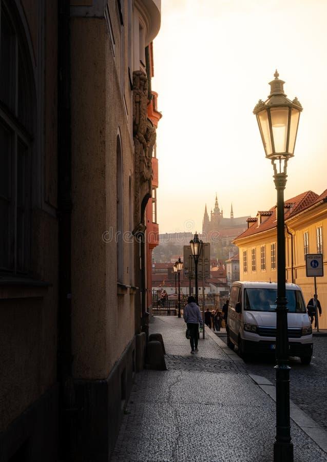 PRAG, TSCHECHISCHE REPUBLIK - 10. APRIL 2019: Prag-Schloss im Abstand hinunter eine klassische tschechische Straße bei Sonnenunte stockbilder