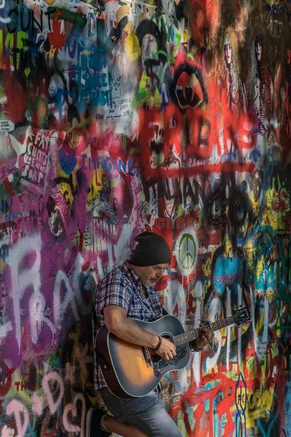 Prag, Tschechische Republik - 10. September 2019: Straße Busker, der an Beatles-Lieder vor John Lennon Wall durchführt lizenzfreies stockbild