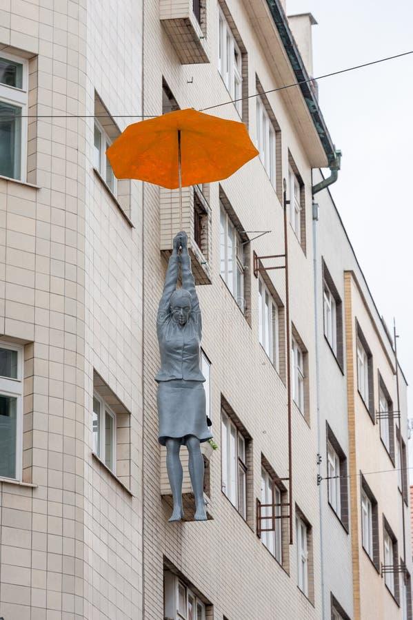 PRAGA, czech - MARZEC 12, 2016: Kobiety obwieszenie parasolem Sztuka występ w Praga, czech obraz stock