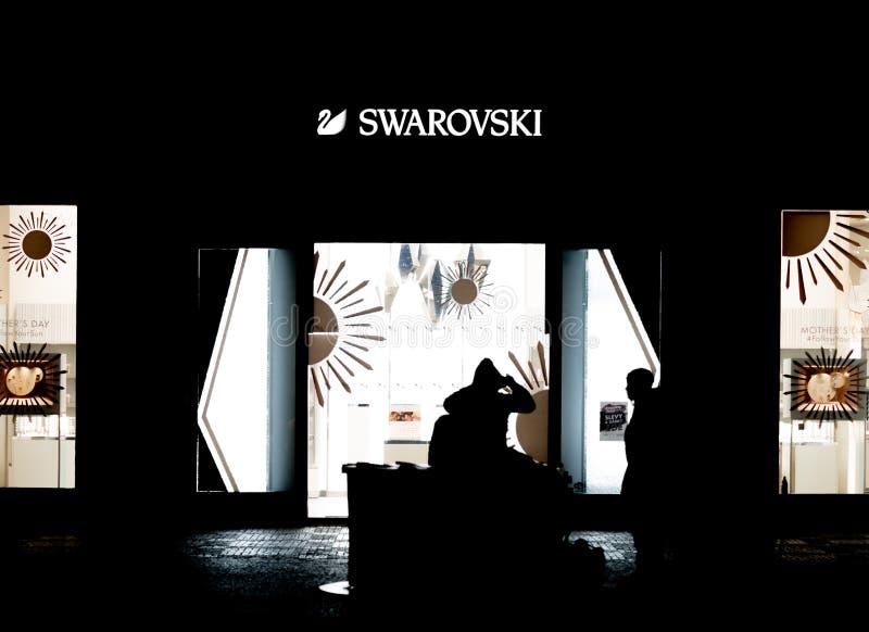 PRAGA, CZECHIA - 10 DE ABRIL DE 2019: Un par se sienta delante de una tienda de Swarovski tarde en la noche en Praga imágenes de archivo libres de regalías