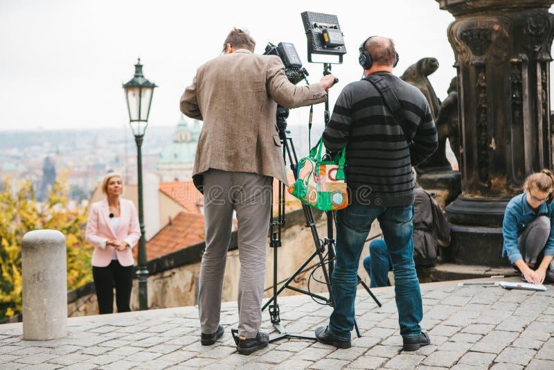 Praga, el 28 de octubre de 2017: El equipo de operadores y los periodistas tiran informe al lado del castillo de Praga fotografía de archivo libre de regalías