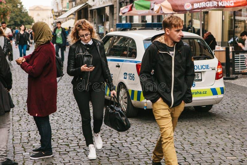 Praga, el 25 de septiembre de 2017: Vida ordinaria en la ciudad La gente camina a lo largo de la calle, al lado del coche policía foto de archivo