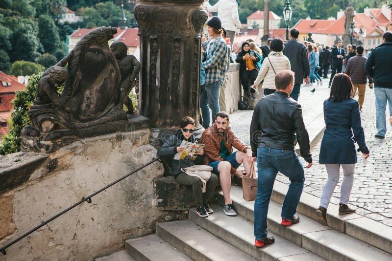 Praga, il 18 settembre 2017: L'uomo stanco e la donna o i turisti si siedono sulle scale e si rilassano L'altra gente è impegnata fotografia stock libera da diritti