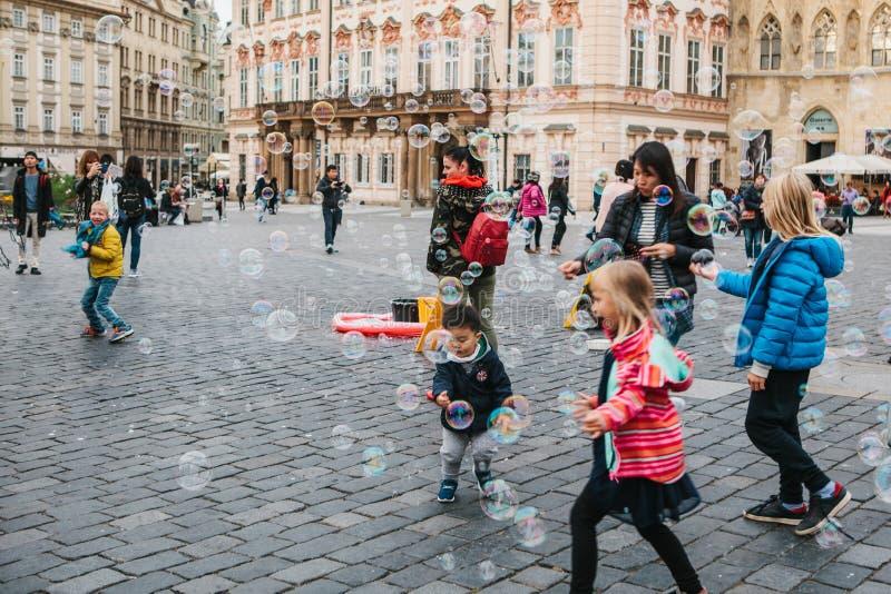 Praga, o 18 de setembro de 2017: As bolhas de sabão do jogo de crianças e exultam na rua da cidade fotografia de stock royalty free