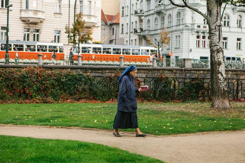 Praga, o 25 de setembro de 2017: Uma freira com a Bíblia Sagrada em sua mão está andando ao longo da estrada abaixo da rua contra foto de stock