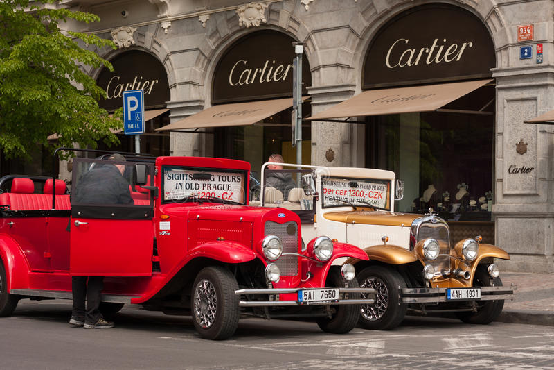 PRAGA, REPÚBLICA CHECA - 21 DE ABRIL DE 2017: Dos coches de Ford del vintage parqueados delante de un Cartier hacen compras en la imagen de archivo libre de regalías
