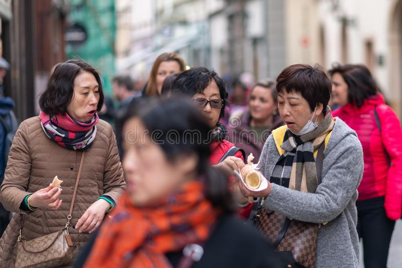 PRAGA, REPÚBLICA CHECA - 12 DE ABRIL DE 2019: Os turistas asiáticos provam o surpreendentemente saboroso schaumrollen o alimento  imagens de stock royalty free
