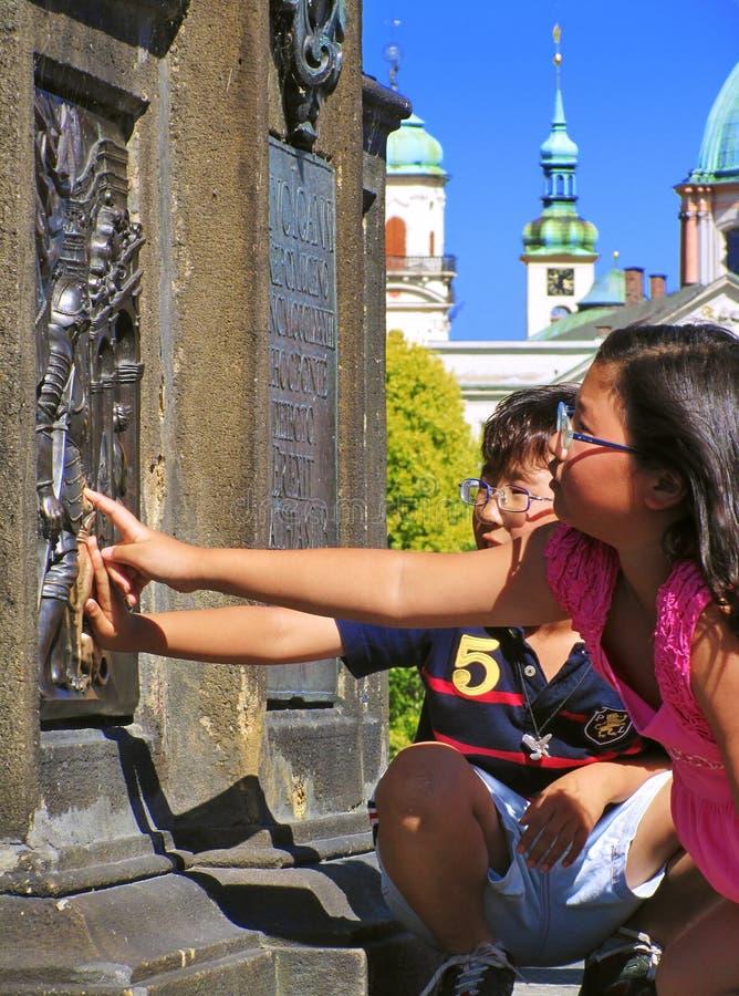 PRAGA, REPÚBLICA CHECA - 29 DE JUNHO DE 2011: Duas crianças tocam no relevo no suporte de St John da estátua de Nepomuk em Charle imagem de stock