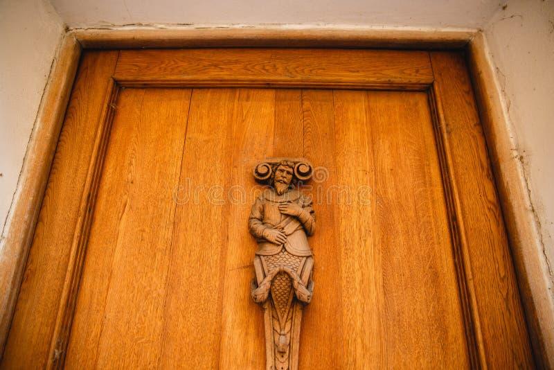 PRAGA, REPÚBLICA CHECA - 23 DE JUNHO DE 2017: figura de madeira do homem na porta imagem de stock