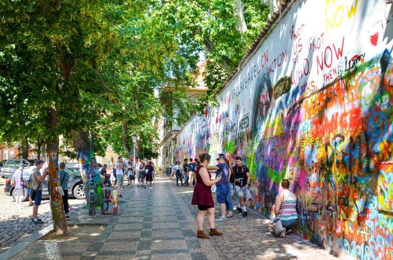 Praga, República Checa - 27 de junho de 2019: Turistas que tomam fotos na frente de John Lennon Wall famoso no centro da capital  imagens de stock royalty free