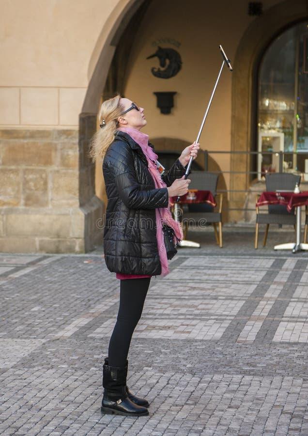 Praga, República Checa - 15 de marzo de 2017: La mujer alegre con la sonrisa que lleva el equipo moderno hace el selfie fotos de archivo libres de regalías