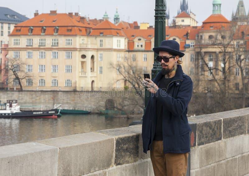 Praga, República Checa - 14 de marzo de 2017: Varón hermoso del inconformista con la barba en mensajes que mandan un SMS de las g imagen de archivo