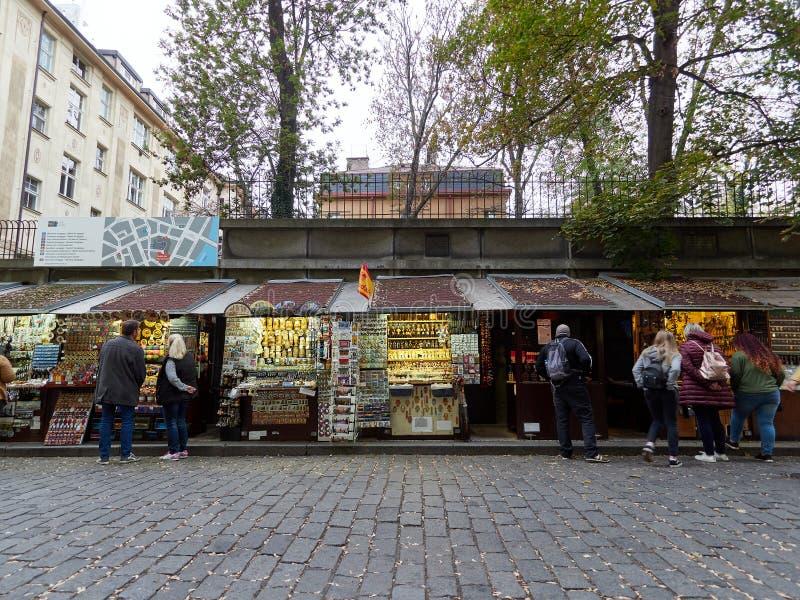 Praga, República Checa - 1 de noviembre de 2018 los turistas miran las paradas que venden los regalos del viaje para el turista e imagen de archivo libre de regalías