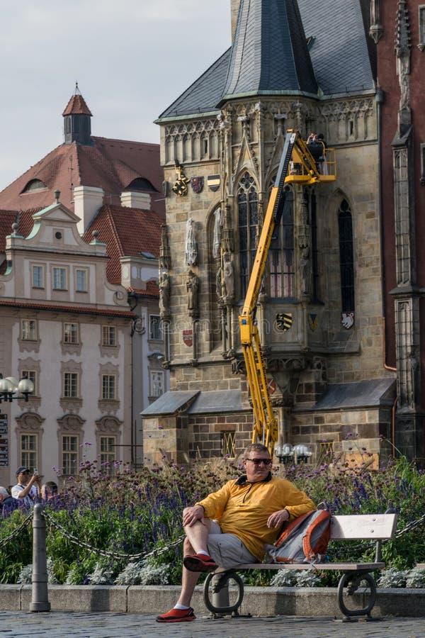 Praga, República Checa - 10 de septiembre de 2019: Reclinación turística sobre un banco en la vieja plaza de los trabajadores del imagen de archivo