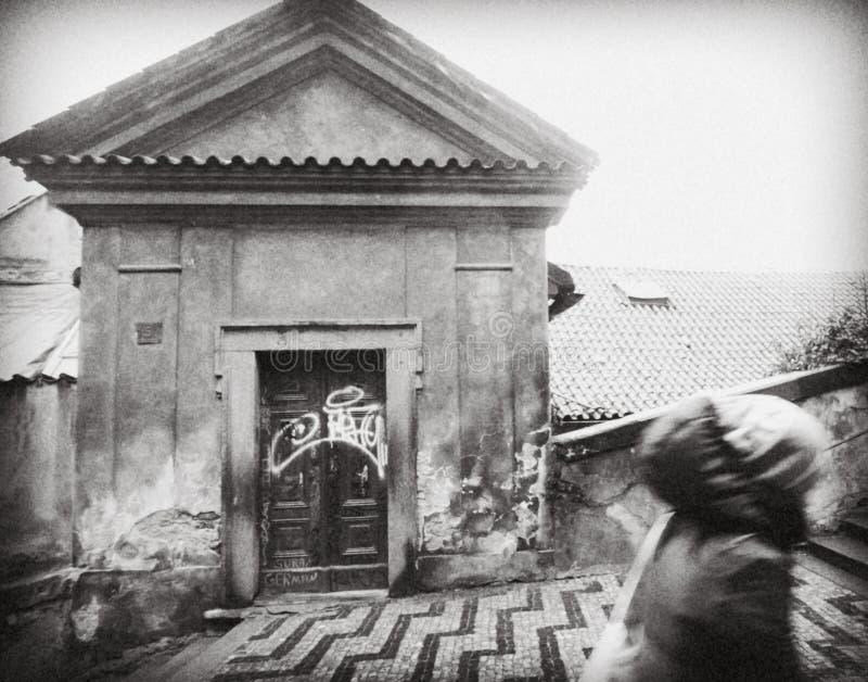 PRAGA, REPÚBLICA CHECA: la muchacha encima de las escaleras, pasando por las casas bajas permeables viejas Las paredes se están d foto de archivo libre de regalías