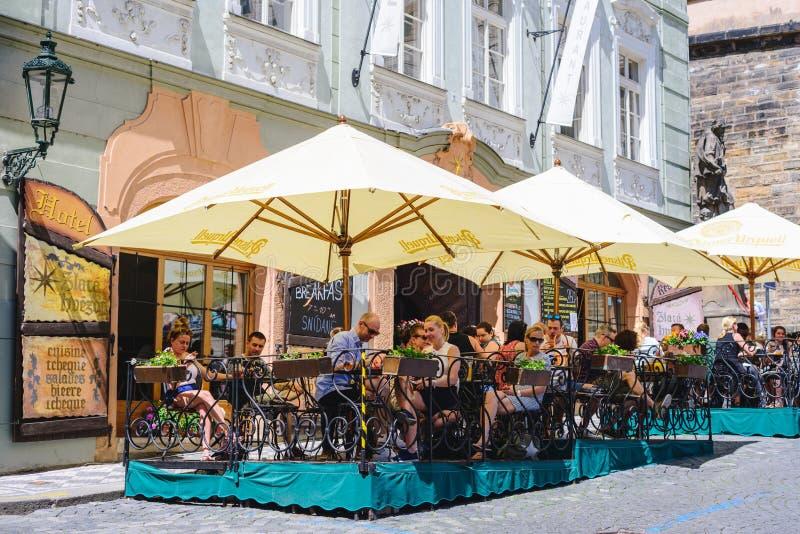 PRAGA, REPÚBLICA CHECA - MAYO DE 2017: Turistas fuera del café, restaurante en la ciudad vieja de Praga imagen de archivo libre de regalías