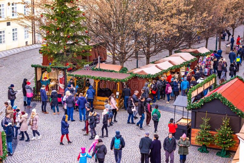Praga, República Checa - 8 12 2018: Mercado de la Navidad en la calle de Praga Árbol de navidad con las pequeñas tiendas de mader imágenes de archivo libres de regalías