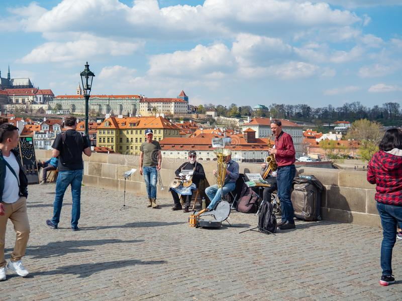 Praga, repubblica Ceca - aprile 2019: Banda musicale della via che gioca sul ponte di Charles Turisti che camminano su Charles Br immagine stock libera da diritti