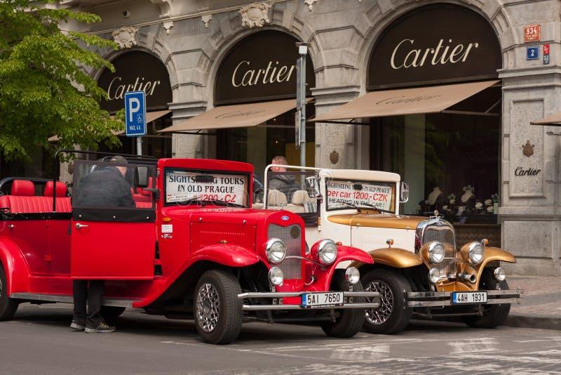 PRAGA, REPUBBLICA CECA - 21 APRILE 2017: Due automobili d'annata di Ford parcheggiate davanti ad un Cartier comperano nella via d immagine stock libera da diritti