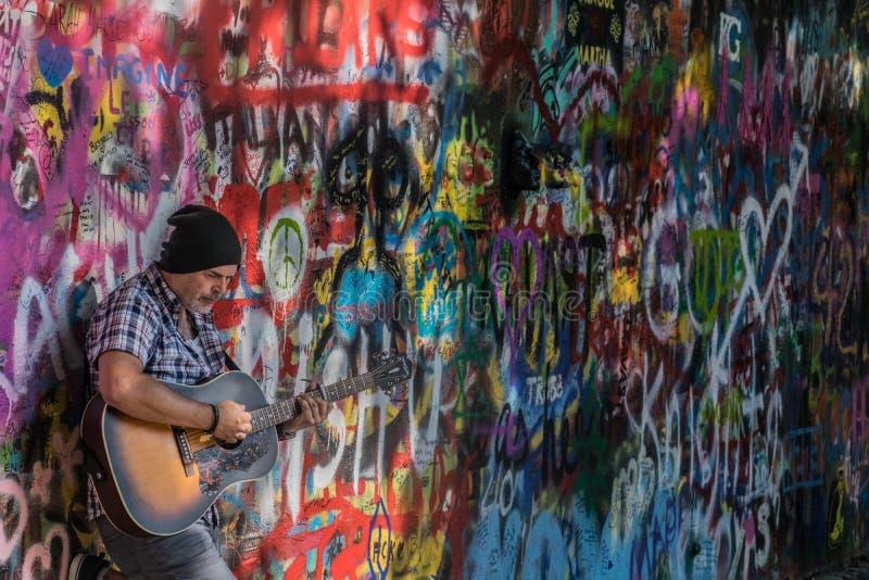 Praga, repubblica Ceca - 10 settembre 2019: Musicista ambulante della via che esegue le canzoni di Beatles davanti a John Lennon  fotografie stock libere da diritti