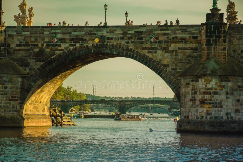 Praga, repubblica Ceca - 17 settembre, 2019: Turisti che camminano trought Charles Bridge, vista dal livello del fiume della Mold fotografia stock libera da diritti