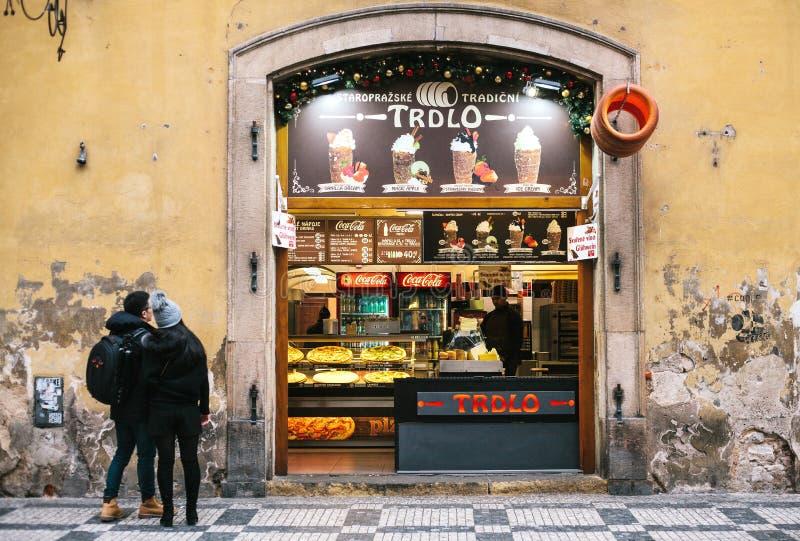 Praga, republika czech, Grudzień 24, 2016: Sklepowy sprzedawanie tradycyjny Czeski słodki karmowy Trdlo Europejski fast food zdjęcia stock