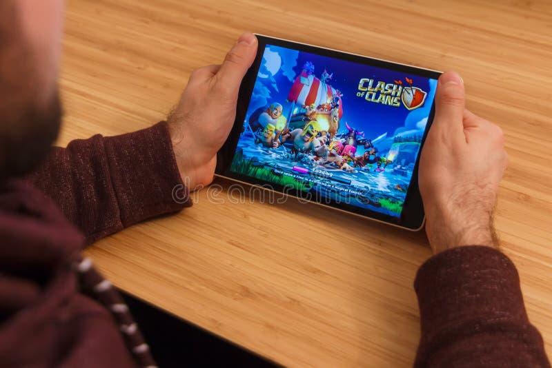 PRAGA, republika czech - MARZEC 16, 2019: Obsługuje trzymać playng i smartphone zderzenie klan wiszącej ozdoby gra Illustrative obraz stock
