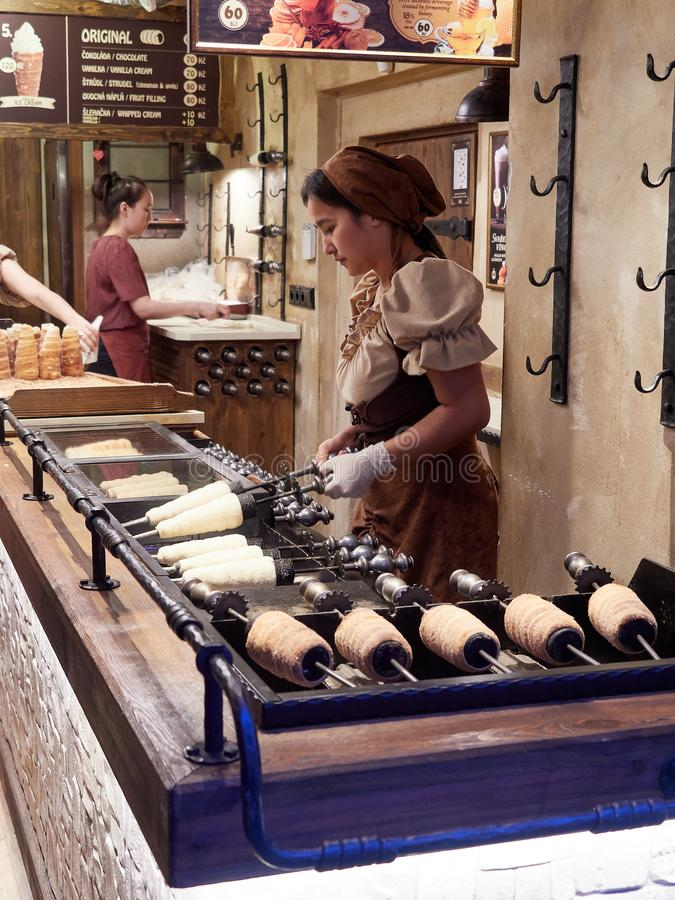Praga, republika czech - Październik 30, 2018, A osoba pracuje w wypracowaniu trdelnÃk, mierzeja tort robić od typ zdjęcia royalty free