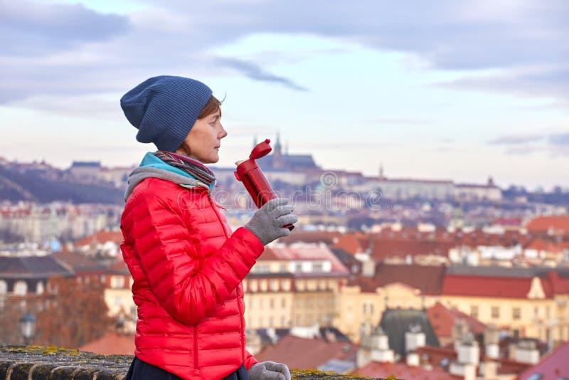praga Una muchacha goza de una vista panorámica de la ciudad vieja y bebe una bebida caliente de un termo imagenes de archivo