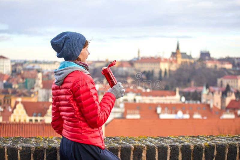 praga Una muchacha goza de una vista panorámica de la ciudad vieja y bebe una bebida caliente de un termo imagen de archivo libre de regalías