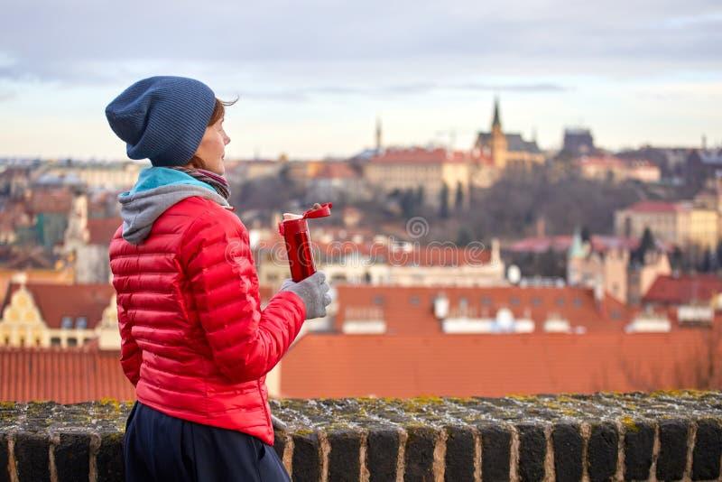 praga Una muchacha goza de una vista panorámica de la ciudad vieja y bebe una bebida caliente de un termo foto de archivo